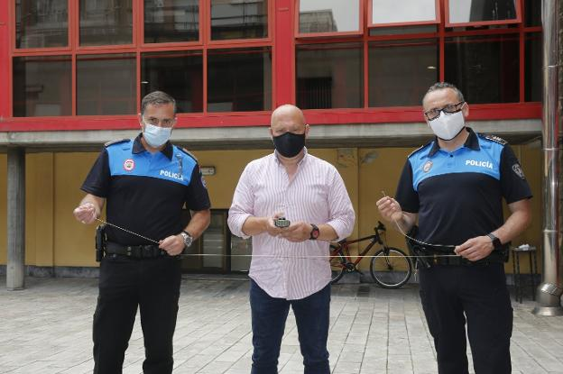 Three Local Police officers show the new tool they will carry (translated). / DAMIÁN ARIENZA